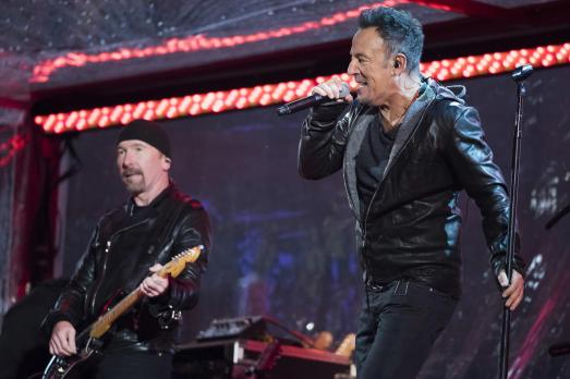 The Edge and Bruce Springsteen perform during the World AIDS Day (RED) concert in Times Square on Monday, Dec. 1, 2014 in New York. (Photo by Charles Sykes/Invision/AP)