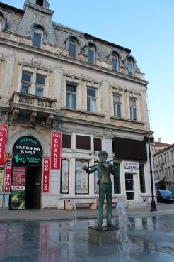 Фонтанът с цигуларчето на един от русенските площади - с типична сграда на заден план и грозни надписи.