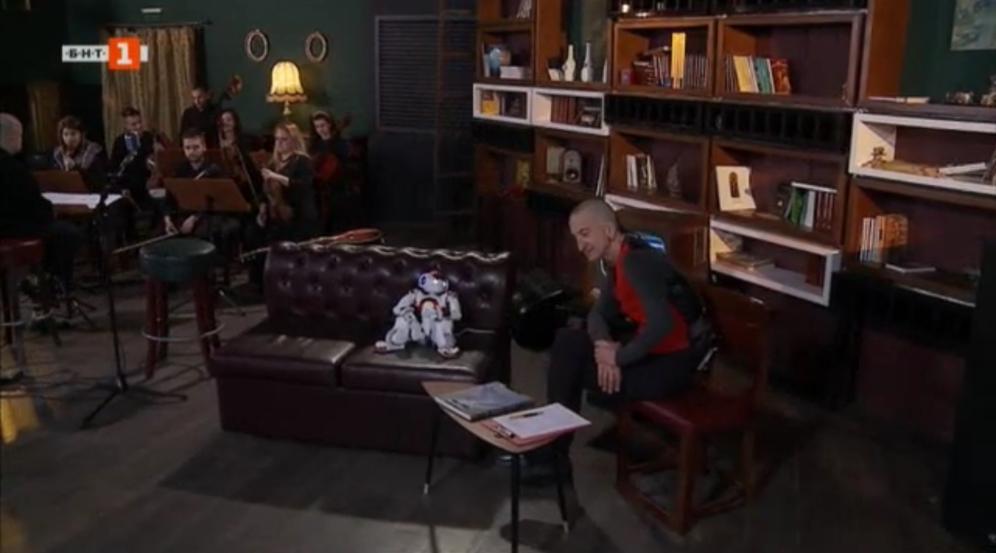 Дони разговаря със своя ко-водещ - робота Питагор - в новото ток-шоу на БНТ. В студиото има и камерен симфоничен оркестър.